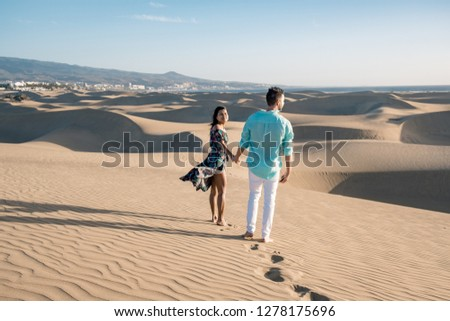 couple walking at the beach of Maspalomas Gran Canaria Spain, men and woman at the sand dunes desert of Maspalomas #1278175696