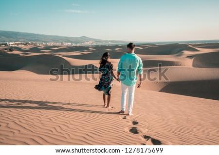 couple walking at the beach of Maspalomas Gran Canaria Spain, men and woman at the sand dunes desert of Maspalomas #1278175699
