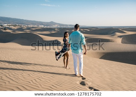 couple walking at the beach of Maspalomas Gran Canaria Spain, men and woman at the sand dunes desert of Maspalomas #1278175702