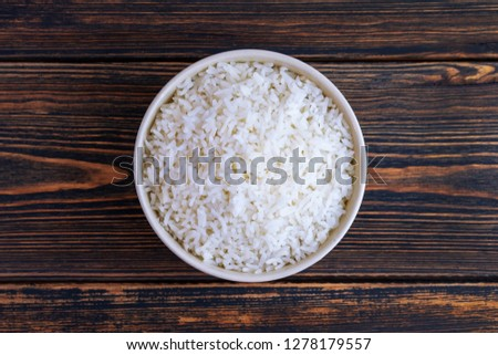 A Cup of white rice on a dark wooden background. Top view. Dietary or vegetarian food. Healthy and proper nutrition. Carbohydrates used by athletes in preparation for the competition. #1278179557