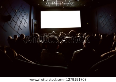 People in the cinema watching a movie. Blank empty white screen. Blurred image #1278181909
