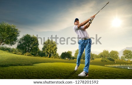 Male golf player on professional golf course. Golfer with golf club taking a shot #1278201592