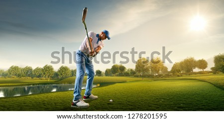 Male golf player on professional golf course. Golfer with golf club taking a shot #1278201595