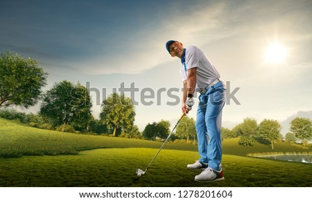 Male golf player on professional golf course. Golfer with golf club taking a shot #1278201604