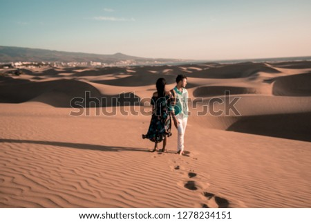 couple walking at the beach of Maspalomas Gran Canaria Spain, men and woman at the sand dunes desert of Maspalomas #1278234151