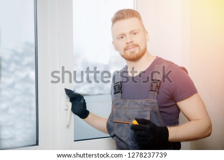 Worker man installs plastic windows and doors with double-glazed white. #1278237739
