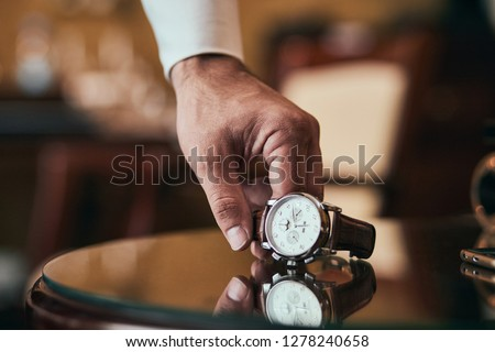 businessman checking time on his wrist watch, man putting clock on hand,groom getting ready in the morning before wedding ceremony #1278240658