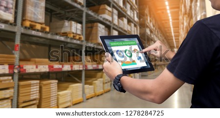 Smart warehouse management system.Worker hands holding tablet on blurred warehouse as background #1278284725