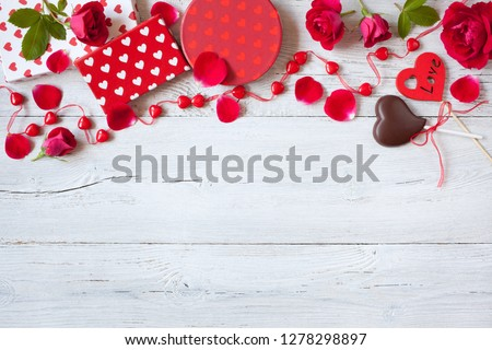 Roses and red hearts on a wooden background and gifts in boxes #1278298897