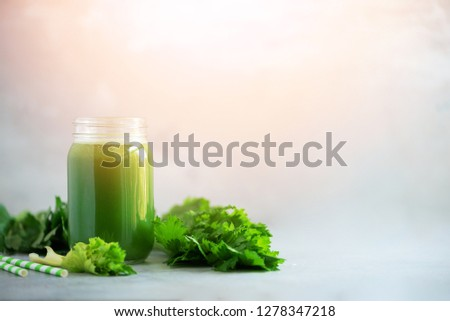 Bottle of green celery smoothie on grey concrete background. Banner with copy space. Square crop. Fresh juice for detox. Vegan, alkaline healthy diet concept. #1278347218