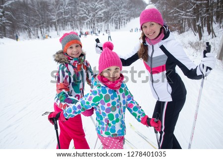Family with two children cross-country skiing in the winter forest in the snow #1278401035