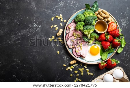 Ketogenic low carbs diet, top view, space for text. Plate on stone black background with keto foods: egg, meat, olive oil, broccoli, berries, nuts, seeds. Healthy fats, clean eating for weight loss #1278421795