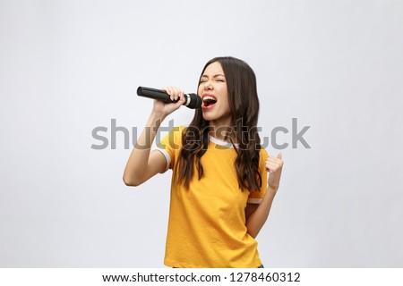 beautiful stylish woman singing karaoke isolated over white background. #1278460312