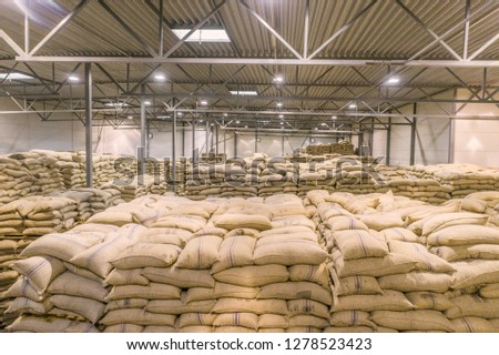 Light huge warehose full of sacks and canvas bags #1278523423