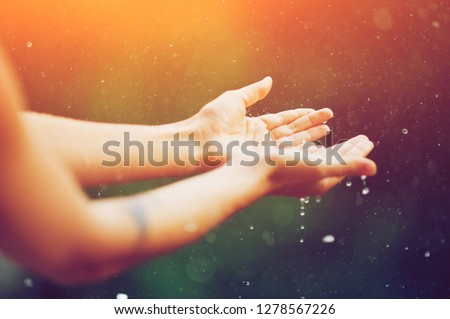 hand catching rain drops on blurred background. Woman hands praying for blessing from god on sunset. Empowerment, sacred forgiveness, positive arm energy, good morning, reborn change calm zen concept. #1278567226