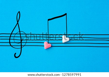 Creative Valentine greeting card. Sugar heart shape candies hand drawn doodle sketch musical notes on staff treble clef on linen texture blue paper background. Love song romantic concept #1278597991