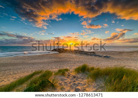 A dramatic landscape photo with clouds framing the sunset as it falls over the beach and ocean
