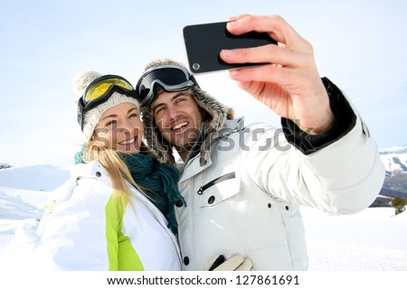 Skiers taking picture of themselves with smartphone