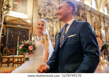 Young beautiful wedding couple at the old catholic church #1278749170