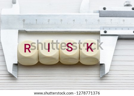 Risk assessment / risk analysis and management concept : Words RISK on wood blocks and a vernier caliper with scales, depict evaluation for financial risk of an investor involved in stock, bond market #1278771376