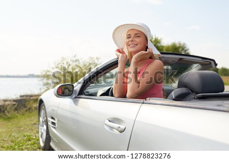 travel, summer holidays, road trip and people concept - happy young woman wearing hat in convertible car enjoying sun #1278823276