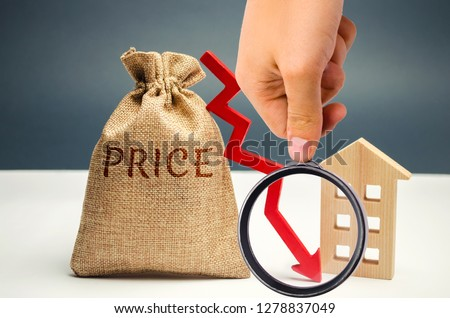 Money bag with word price, down arrow and wooden house. The concept of falling property prices. Lower housing prices. Low rent. The decline in the value of the property. Low utility prices #1278837049