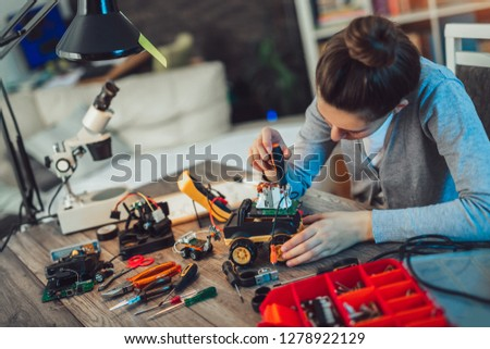 Girl constructs technical toy. Technical toy on table full of details #1278922129