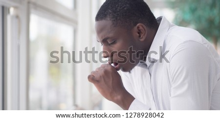 Sick African man coughing; Portrait of ill black man cough due to cold, flu, allergy, polluted air, fine dust, tuberculosis; air pollution, lung cancer, emphysema concept; African man model Royalty-Free Stock Photo #1278928042