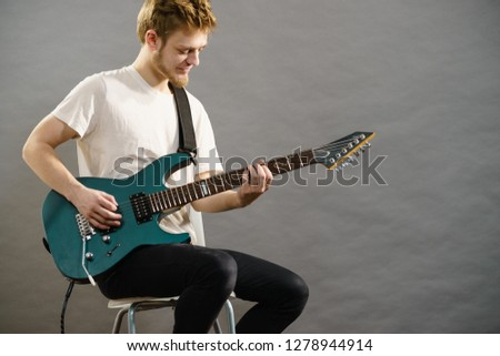 Man playing on electric guitar during gig. Musical instrument. Teenage boy having music hobby. #1278944914