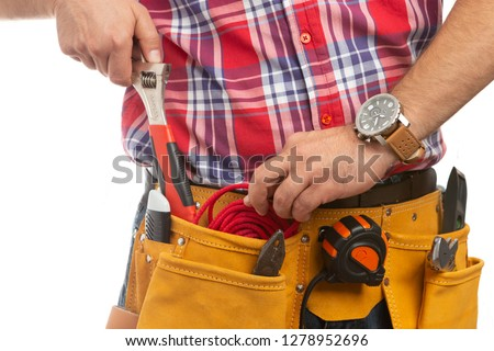 Close-up of male construction worker putting red rope back in pocket while holding wrench in hand with wrist watch isolated on white background #1278952696