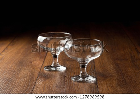 empty glass cups on a brown wooden background, tableware. #1278969598