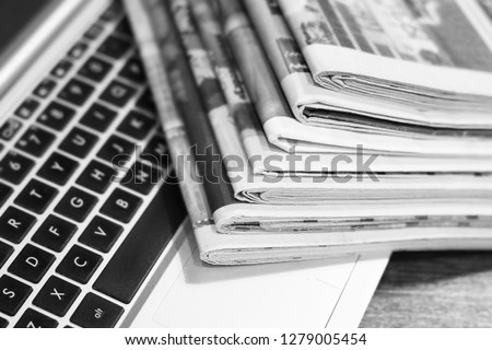 Newspapers and laptop. Pile of daily papers with news on the computer. Pages with headlines, articles folded and stacked on keypad of electronic device. Modern gadget and old journals, focus on paper  #1279005454