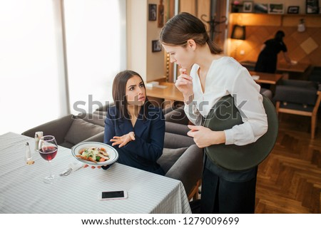 Upset yougn businesswoman complain about bowl with salad. She hold it in hands and point. Customer look at waitress. Young woman in white blouse is upset. #1279009699