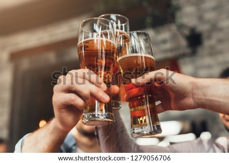 Friends toasting with glasses of beer, resting at the pub, closeup #1279056706