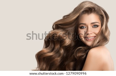 Portrait of beautiful cute woman with curly brown long hair. Gray background. #1279090996