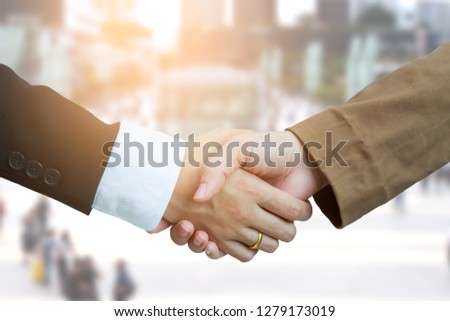 Close of business people shaking hands as symbol for partnership, finishing up a meeting Handshake Business Deal Negotiating concept. Mixed media #1279173019