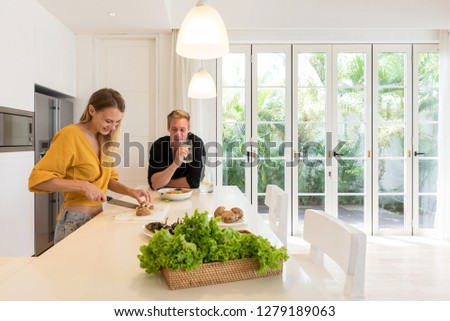 Couple making lunch on a white island kitchen at home #1279189063