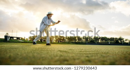 Old gentleman in hat in position to throw a boules in a lawn. Man playing boules in a playground with sun flare in the background. #1279230643