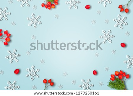 Christmas or winter composition. Frame made of snowflakes and red berries on pastel blue background. Christmas, winter, new year concept. Flat lay, top view, copy space #1279250161