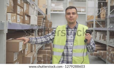 Portrait man store worker using bar code scanner scanning labels on boxes #1279288603