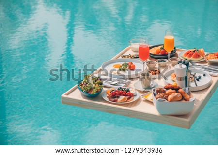 Breakfast in swimming pool, floating breakfast in tropical resort. Table relaxing in calm pool water, healthy breakfast and fruit plate by resort pool. Exotic summer diet. Tropical beach lifestyle #1279343986