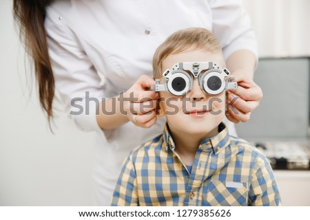 Portrait little blond boy with smile in shirt. hand doctor kept his face special sunglasses for eye tests and selection of lenses #1279385626
