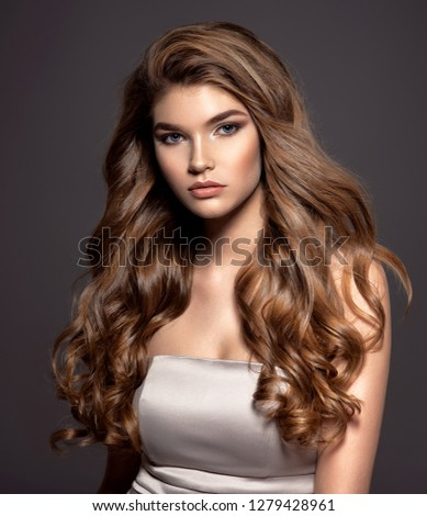 Young brown-haired woman with long curly hair. Beautiful face of gorgeous girl with blue eyes. Nice portrait of a caucasian female looking at camera. Attractive fashion model