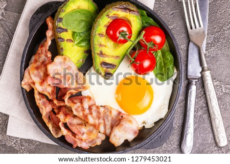 Grilled bacon and avocado, fried eggs with spinach and cherry tomatoes in cast-iron pan. Gray concrete background. Top view. Ketogenic diet. Low carb high fat breakfast. Healthy food concept #1279453021
