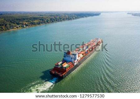 Aerial view of a container ship going upstream in the St. Lawrence River near the port of Montreal in Canada #1279577530