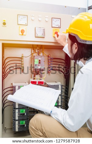 Close up of young Asian electric engineer in beige pant and white shirt, wear yellow helmet, squat near control panel, working instruction in hand, follow up his routine daily checking #1279587928
