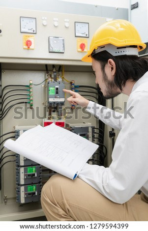 Close up of young Asian electric engineer in beige pant and white shirt, wear yellow helmet, squat near control panel, working instruction in hand, follow up his routine daily checking #1279594399