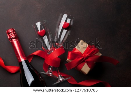 Valentine's day greeting card with champagne glasses and candy hearts on stone background. Top view with space for your greetings. Flat lay #1279610785