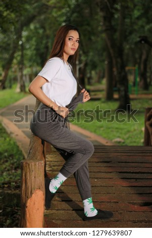 Women with long hair at the park. Sporty look fashion inspiration. #1279639807
