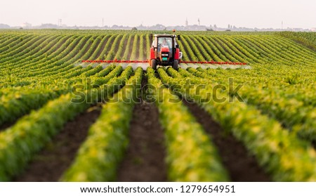 Tractor spraying a field of soybean #1279654951